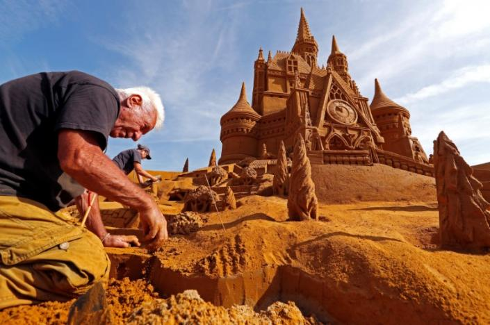 "Sand carver Daga works on a sculpture during the Sand Sculpture Festival ""Disney Sand Magic"" in Ostend"