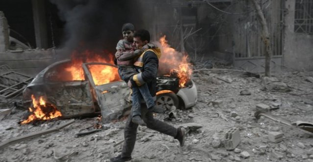 A Syrian paramedic carries an injured child following reported bombardment