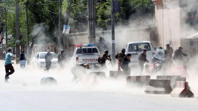 Afghan security forces run from a second suicide attack in Kabul Monday