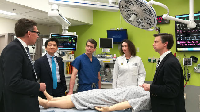 The team of surgeons gather around a mannequin at Johns Hopkins,