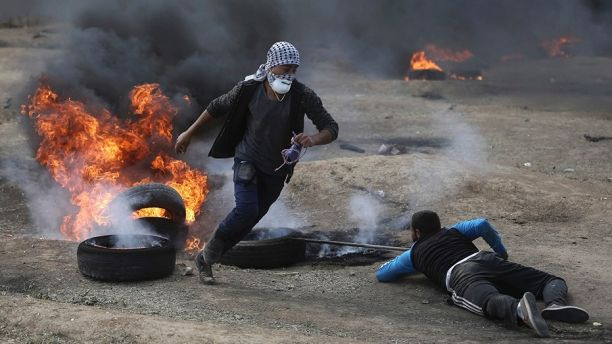 Palestinian protesters burn tires during a protest on the Gaza Strip's