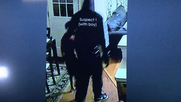 One of the suspects can be seen leading the couple's 7-year-old son around the home looking for money.  (FOX26)