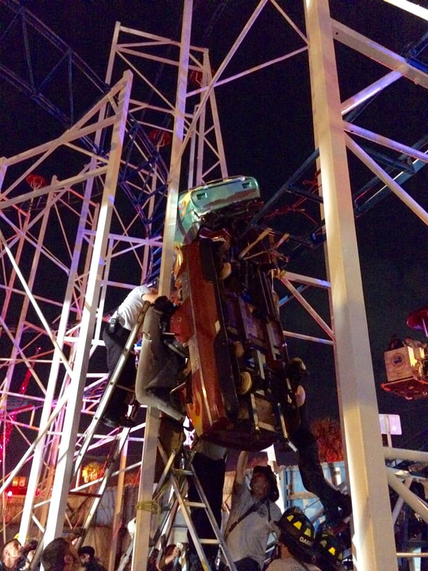 Daytona Beach firefighters work to rescue two rollercoaster riders after their car derailed on the Daytona Beach boardwal