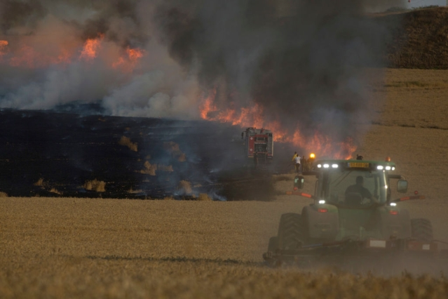 Firefighters and soldiers attempt to extinguish a fire in a wheat field in Nahal Oz, Israel,
