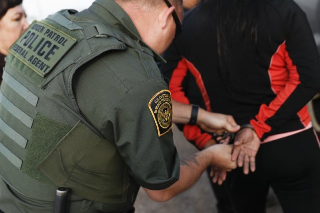 A Government agent takes a suspect into custody during an immigration sting