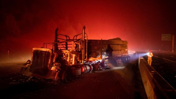 A scorched logging truck rests on Interstate 5 as the Delta Fire burns