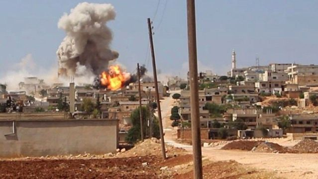 shows flames and smoke rising from a Syrian government airstrike, in Hobeit village,