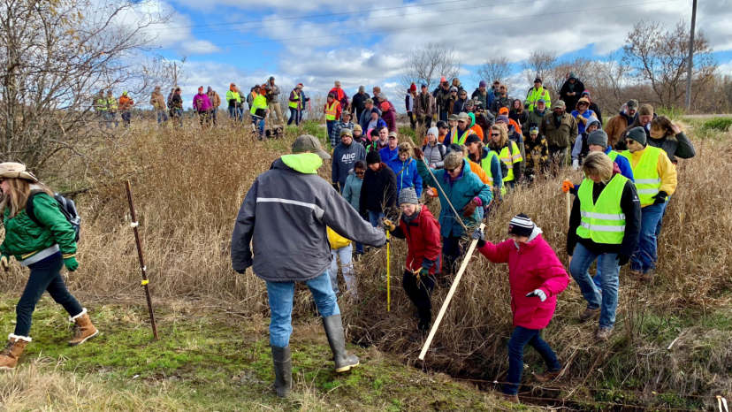 Volunteers cross a creek and barbed wire near Barron, Wis.,