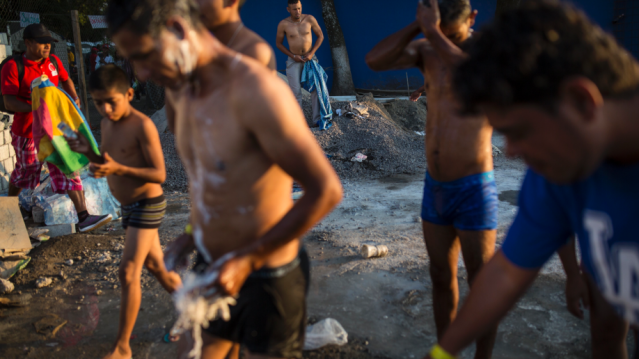 Central American migrants shower in a makeshift shelter in Irapuato, Mexico,
