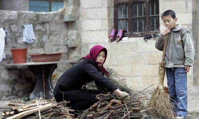 A woman farmer tieing a bunch of firewood as her son watches