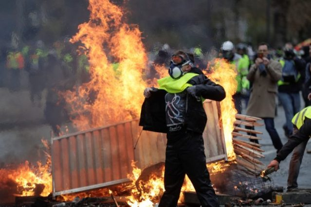 A demonstrator walks past a fire during a Gilets jaunes protest in Paris