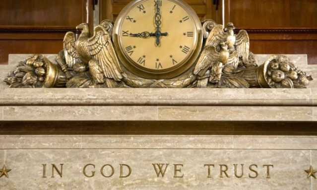 "A clock and the motto ""In God We Trust"""