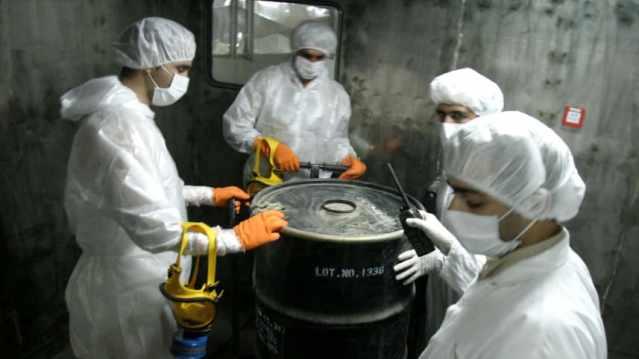 """FILE PHOTO: Iranian technicians lift a barrel of """"yellow cake"""""""