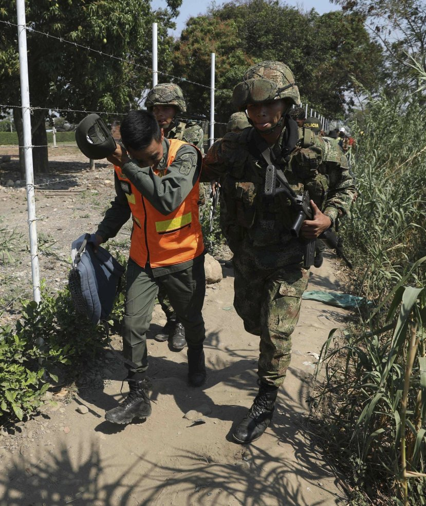 A Colombian soldier escorts a Venezuelan National Guard who deserted his post