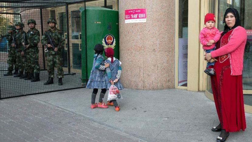 Uighur woman carries a toddler