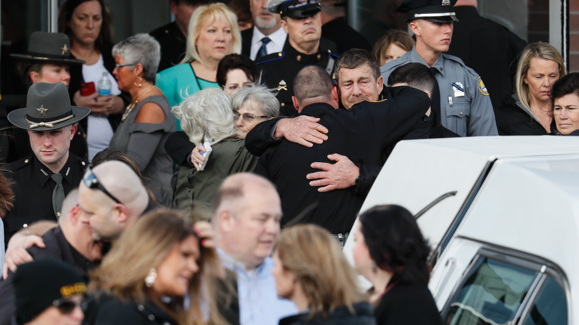 Officers and mourners react after the casket of Detective Bill Brewer,