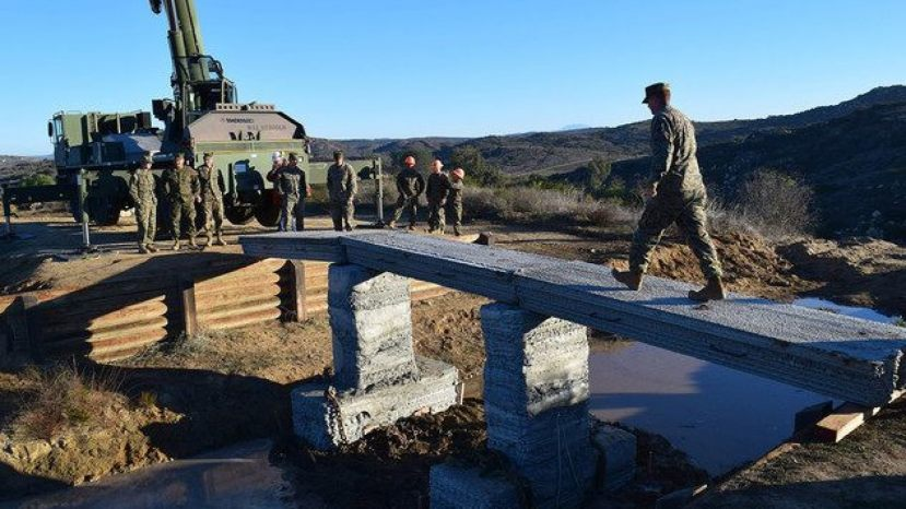 A Marine with 1st Marine Logistics Group walks across the 3D-printed concrete footbridge