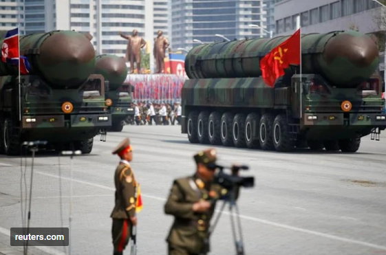 Intercontinental ballistic missiles (ICBM) are driven past the stand with North Korean leader Kim Jong Un