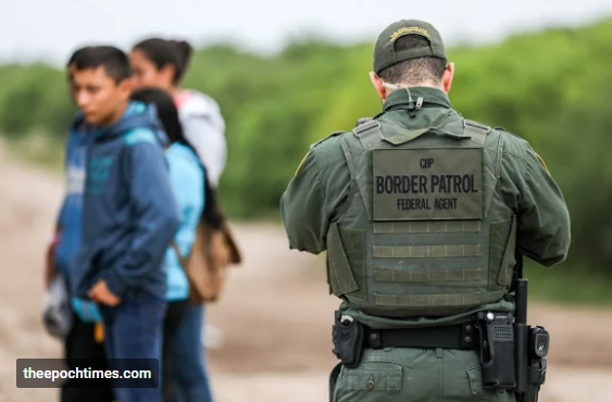 A Border Patrol agent apprehends illegal aliens