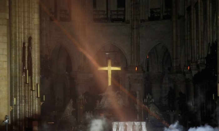 Smoke rises around the alter in front of the cross inside the Notre-Dame Cathedral