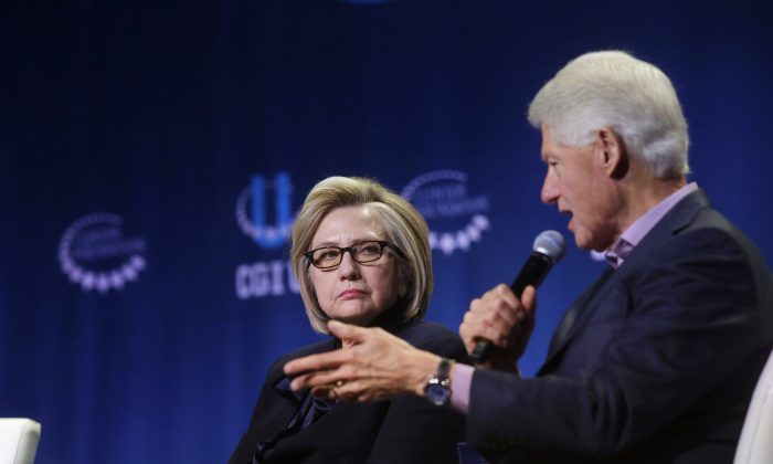 Former Secretary of State Hillary Clinton listens as former President Bill Clinton speaks
