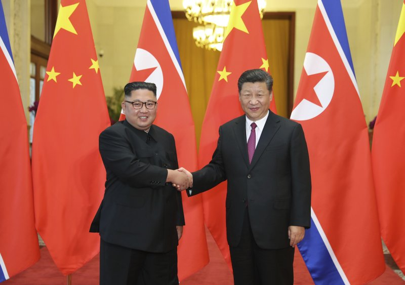 Chinese President Xi Jinping, right, poses with North Korean leader Kim Jong Un