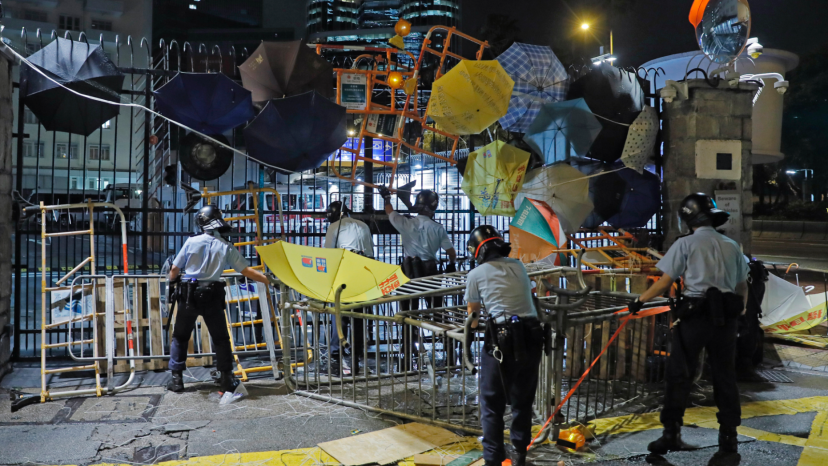 Riot police clear barricades blocked by protesters outside the police headquarters