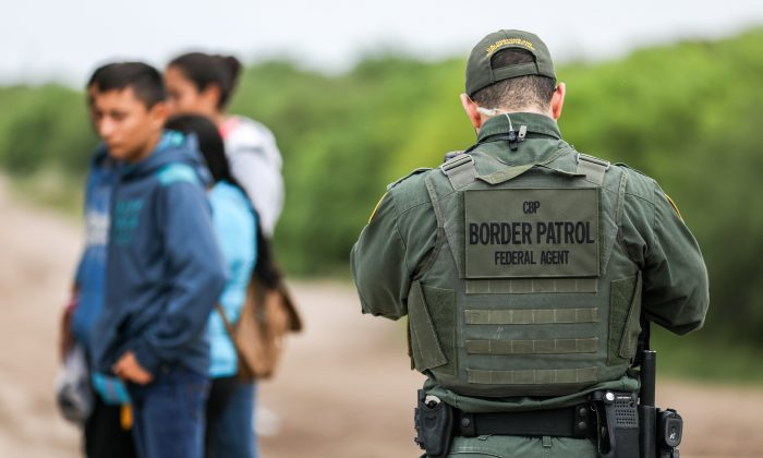 A Border Patrol agent apprehends illegal aliens