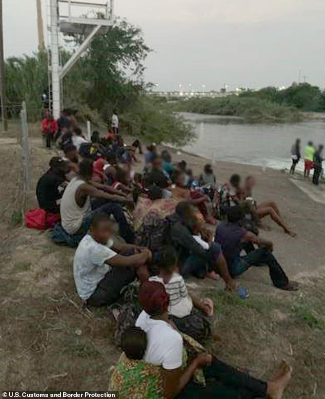The apprehended migrants pictured above after they were detained by border patrol agents.