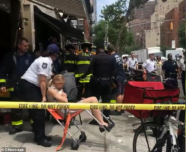 A woman is shown being taken away from the scene in a wheelchair.