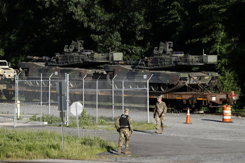 Military police walk near Abrams tanks on a flat car in a rail yard, Monday, July 1, 2019,