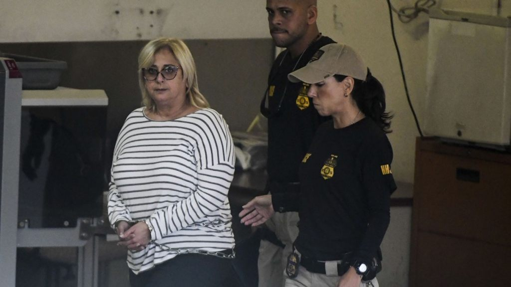 Federal agents escort former Puerto Rico Health Insurance Administration head Ángela Ávila-Marrero, who was arrested in San Juan, Puerto Rico,