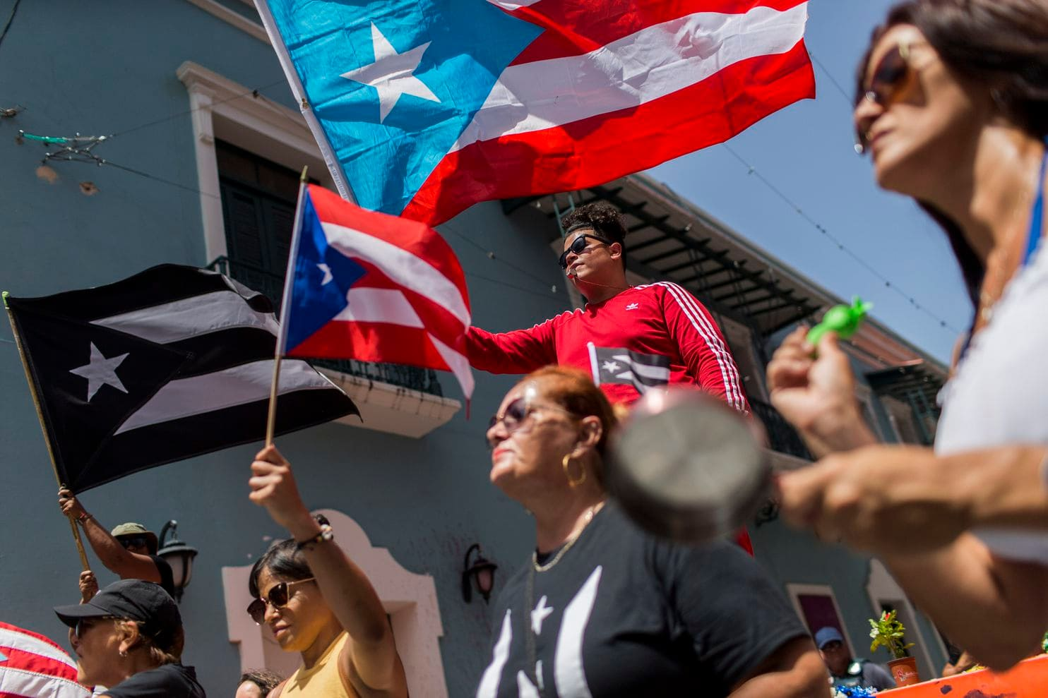 Demonstrators, some waving Puerto Rican national flags, gather in front of the governor's mansion