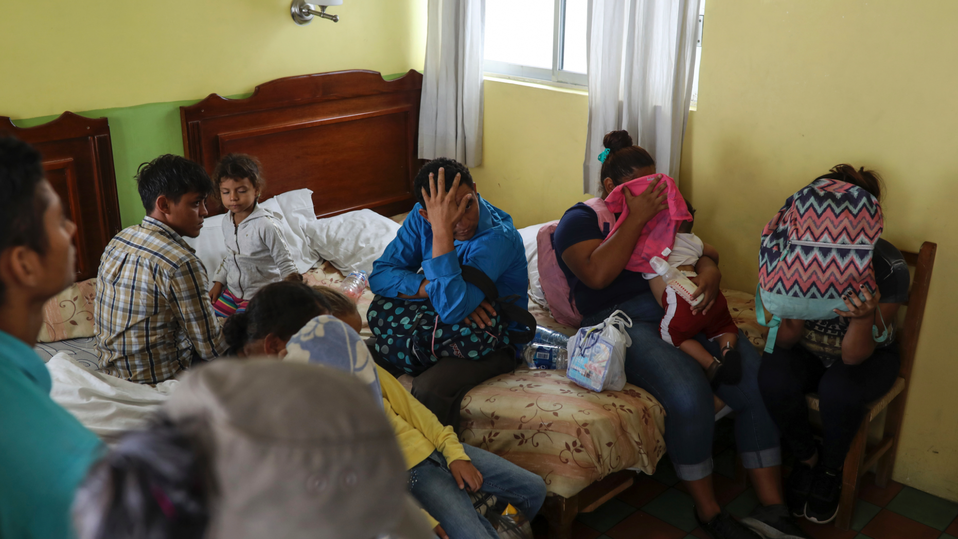 Central American migrants sit together inside a room at the Latino hotel during a raid by Mexican immigration agents