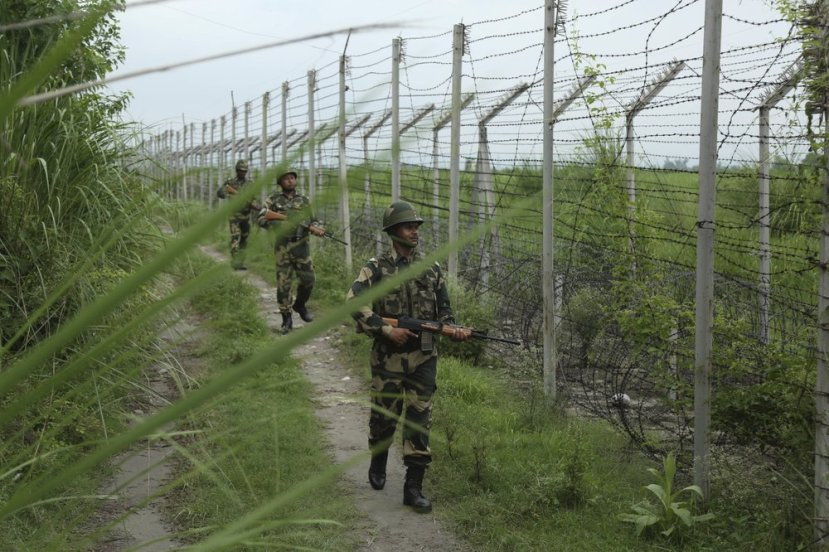 India's Border Security Force (BSF) soldiers patrol near the India Pakistan border fencing at Garkhal in Akhnoor,