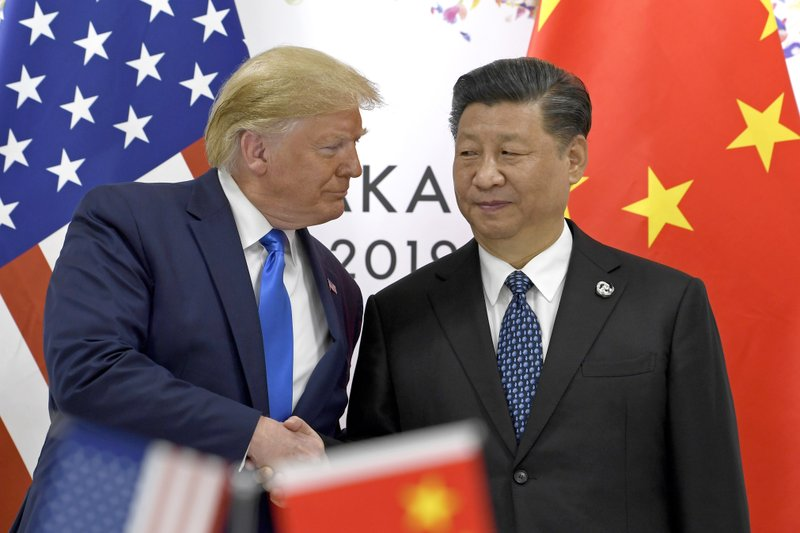 FILE - In this June 29, 2019, file photo, U.S. President Donald Trump, left, shakes hands with Chinese President Xi Jinping during a meeting on the sidelines of the G-20 summit in Osaka, western Japan