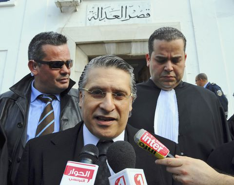 FILE - In this Jan.23 2012 file photo, the owner of the Tunisian private channel Nessma TV, Nabil Karoui, center, leaves the Tunis courthouse after attending his trial