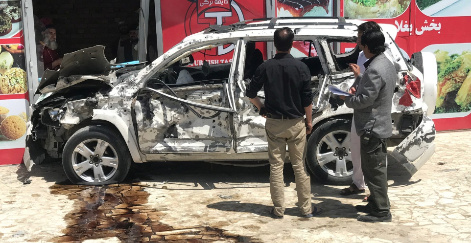Afghans look at at a car hit damaged a suicide bomb blast in Kabul, Afghanistan May 31, 2019