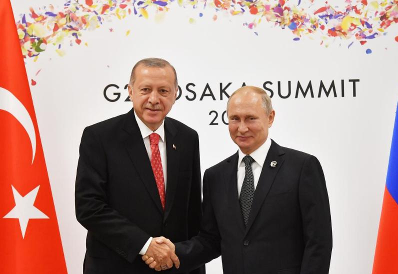 Russian President Vladimir Putin (R) shakes hands with Turkish President Recep Tayyip Erdogan