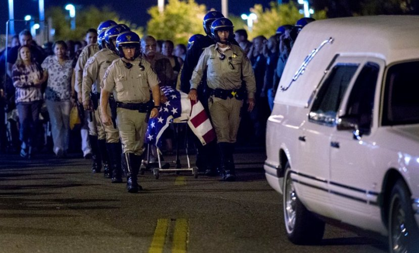 Slain CHP officer Andre Moye is transported to a hearse as his family follows from the Riverside University Health Systems Medical Center after he was shot and killed while two fellow officers were wounded during a traffic stop on the Eastridge Avenue overpass over the 215 Freeway around 5:30 p.m. on Monday, Aug 12, 2019.