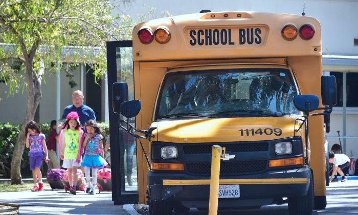 Children walk past a School Bus in Monterey Park, California on April 28, 2017.