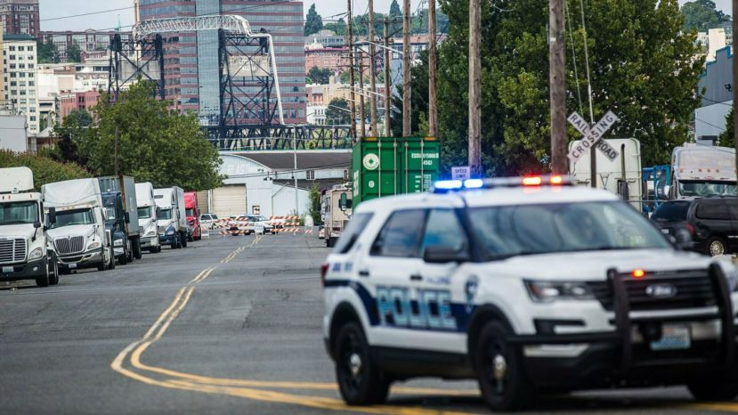 A police officer guards the front of a road block near the Northwest Detention Center Saturday in Tacoma, Wash