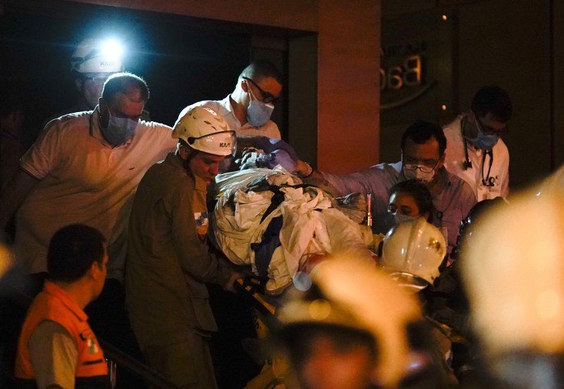 A patient is evacuated from a burning hospital in Rio de Janeiro, Brazil, Thursday, Sept. 12, 2019.