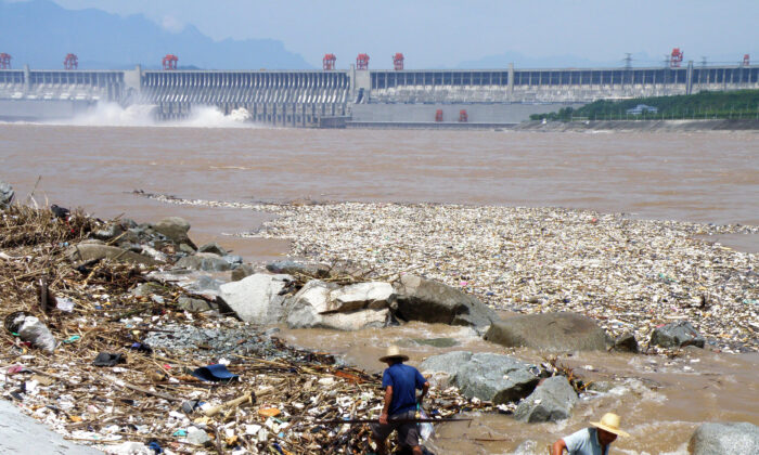 Two workers clean up trash along the bank of the Yangtze River near the Three Gorges Dam in Yichang, in central China's Hubei Province on Aug. 1, 2010.