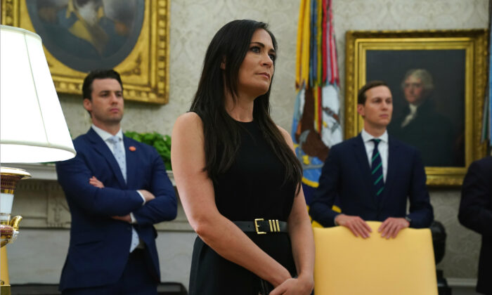 """White House Press Secretary Stephanie Grisham listens during a signing of a """"safe third country"""" agreement in the Oval Office of the White House in Washington on July 26, 2019."""