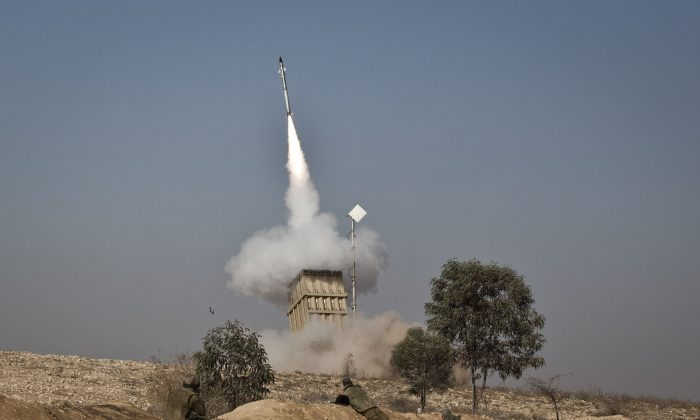 An Israeli soldier lies on the ground as missiles are fired from an Iron Dome anti-missile station near the city of Beer Sheva, Israel on Nov. 15, 2012.
