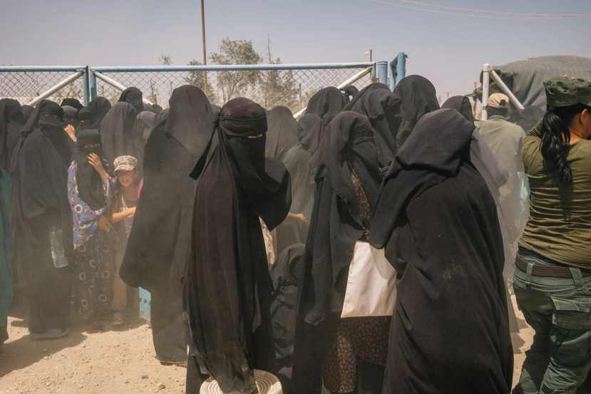Women and children stand by a gate during a brief dust storm at the foreigners' section of al-Hol camp.