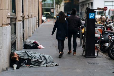 SAN FRANCISCO, CA - AUGUST 23: People walk by homeless people sleeping n San Francisco, California, on August 23, 2018.