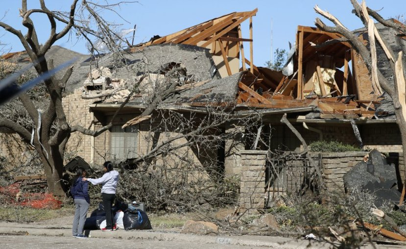 Women stand outside a house damaged by a tornado in the Preston Hollow section of Dallas, Monday, Oct. 21, 2019