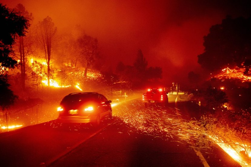 Embers fly across a roadway as the Kincade Fire burns through the Jimtown community of Sonoma County, Calif., on Thursday, Oct. 24, 2019.